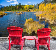 Two red deck chairs on the lake Royalty Free Stock Photos