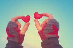 Two red decorative hearts in female hands against the background of the sky. Romantic background Stock Image