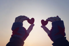 Two red decorative hearts in female hands against the background of the sky. Romantic background Stock Photography
