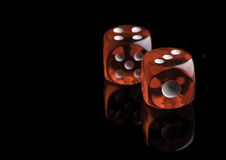 Two red dice on black background stock images