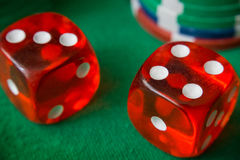 Two red dice fall 7, casino chips, cards on green felt. Red casino dice rolls and casino chips on green table stock photo