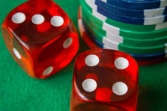 Two red dice fall 7, casino chips, cards on green felt. Red casino dice rolls and casino chips on green table stock image