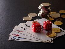 Two red dice, game cards and stack of coins Royalty Free Stock Photo