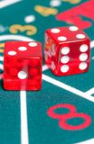 Two red dice on green gambling game Stock Photography