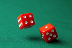 Two red dice on green poker gaming table in casino. Concept online gambling royalty free stock photos