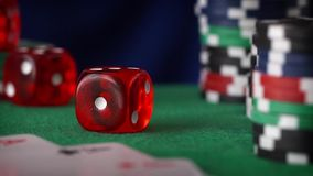 Two red dice rolls in hand, casino chips, cards on green felt. Two red casino dice rolls and casino chips on green table stock footage