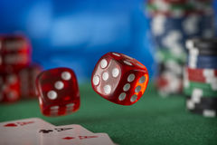 Two red dice rotates in the air, casino chips, cards on green felt Stock Photo