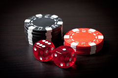 Two red dices and black and red chips Stock Photos