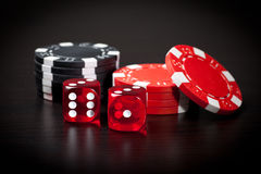 Two red dices and black and red chips Royalty Free Stock Image