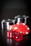 Two red dices and black and red chips Stock Photography