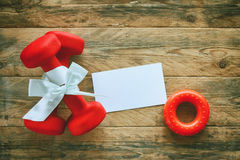 Two red dumbbell with gift bow, paper tag, carpal expander. Two red dumbbell with a gift bow and blank paper tag, carpal expander on a wooden planks, sport Stock Images