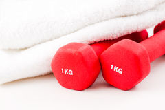 Two red dumbbells and white towel stock photo