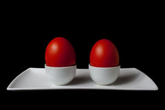 Two Red Easter Eggs on White Plate Stock Photos