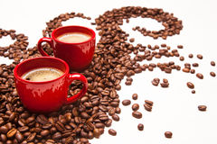 Two red espresso cups with coffee beans Stock Images