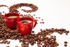 Two red espresso cups with coffee beans Royalty Free Stock Images