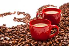 Two red espresso cups with coffee beans Royalty Free Stock Photos