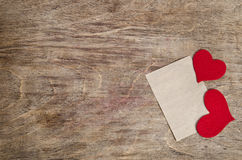 Two Red fabric hearts with sheet of paper Stock Image