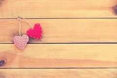 Two red fabric hearts on wood background, vintage process. Two red fabric hearts on old wood background, vintage process royalty free stock image