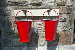 Two red fire buckets against a stone wall background. Two dented vintage fire buckets against a stone wall background royalty free stock photography