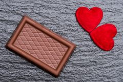 Two red fluffy hearts and a chocolate confection over rough black slate background. Romance concept: Two red fluffy hearts and a chocolate confection served on Royalty Free Stock Photos