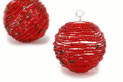 Two red glass christmas ornaments. Two red glass beaded ornaments - isoalted on a white background Royalty Free Stock Images