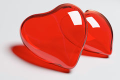 Two red glass hearts. On the white Royalty Free Stock Photography