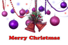 Two red glitter bells hanging on a tartan ribbon with christmas baubles with a snowy Merry Christmas sign Royalty Free Stock Photo