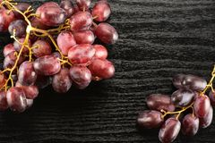 Fresh raw red wine grapes on black wood. Two red globe grape clusters table top isolated on black wood background dark pink berries Stock Photo