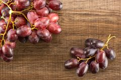 Fresh raw red wine grapes on brown wood. Two red globe grape clusters table top isolated on brown wood background dark pink berries Royalty Free Stock Photos
