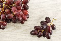 Fresh raw red wine grapes on grey wood. Two red globe grape clusters table top isolated on grey wood background dark pink berries Royalty Free Stock Photos