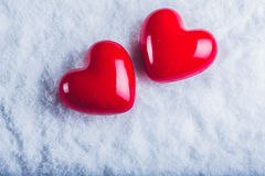 Two red glossy hearts on a frosty white snow background. Love and St. Valentine concept. Royalty Free Stock Photo