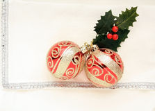 Two red and gold  Christmas balls and holly leaves. Two red and gold  Christmas baubles or balls sitting on top of a silver and white napkin with a holly leaf or Stock Images
