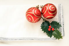 Two red and gold  Christmas balls on white background. Two red and gold Christmas baubles and holly leaves sitting on top of a silver and white napkin on a white Stock Photo