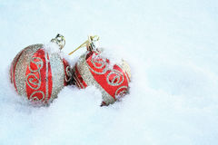Two red and gold Colorful Christmas balls in snow Stock Images