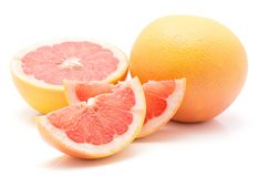 Red grapefruit isolated. Two red grapefruit slices, one half and one whole isolated on white background Royalty Free Stock Photography