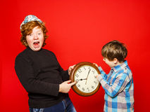 Two red-hair brothers posing with big clock Royalty Free Stock Image