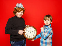 Two red-hair brothers posing with big clock Stock Images