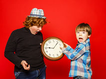 Two red-hair brothers posing with big clock Stock Photography