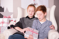 Two red haired children are looking on their gift Stock Photography