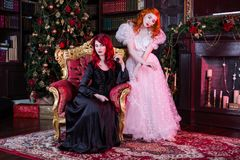 Two beautiful girls with red hair in a beautiful white wedding Victorian dresses. Two red-haired girl near the fireplace and the Christmas tree. Fairy and Witch Royalty Free Stock Photography