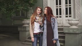 Two red-haired girlfriends listening to music on headphones with a mobile phone on the street. Red-haired girl wears headphones and listens to music in the stock video footage