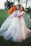 Two red-haired girls in free dresses of tulle on the background of a summer ravine. Two slender models posing in nature royalty free stock photo