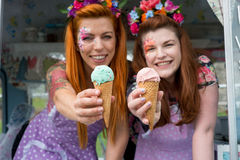 Two red haired ladies holding ice cream from van. Two red haired ladies smiling wearing vintage spotted dresses holding ice cream out of van with blurred stock photography