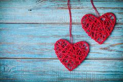Two red heart hanging on turquoise vintage wall for Valentines day card