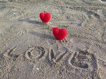 Two red heart. The inscription on the sand. Love. Stock Photos