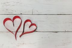 Two Red heart made of ribbon on a wooden background using as lov Royalty Free Stock Photos