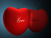 Two red heart pendents with gold inscription love Royalty Free Stock Photo
