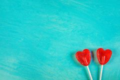 Two Red Heart Shape Candy Lollipops on Sticks on Turquoise Background Corner Position. Valentine Romantic Love Greeting Card Royalty Free Stock Photos