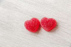 Two red heart shape jelly candy.white wooden table.space for tex. T Royalty Free Stock Photography