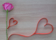 Two red heart shape ribbon with pink rose on wooden surface with space for text Stock Photography